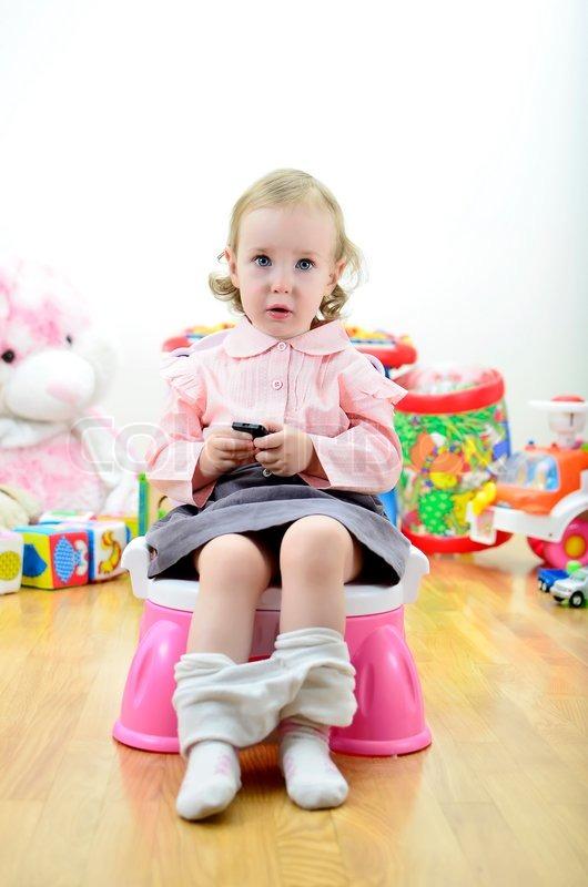 kleines m dchen sitzt auf dem t pfchen mit einer fernbedienung oder handy in der hand. Black Bedroom Furniture Sets. Home Design Ideas