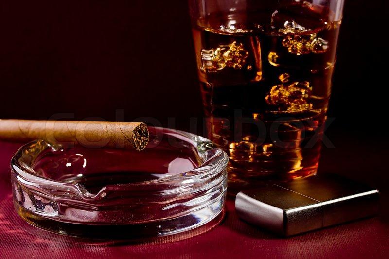 close up selektiven fokus einer braunen zigarre und silber feuerzeug mit einem glas whisky in. Black Bedroom Furniture Sets. Home Design Ideas