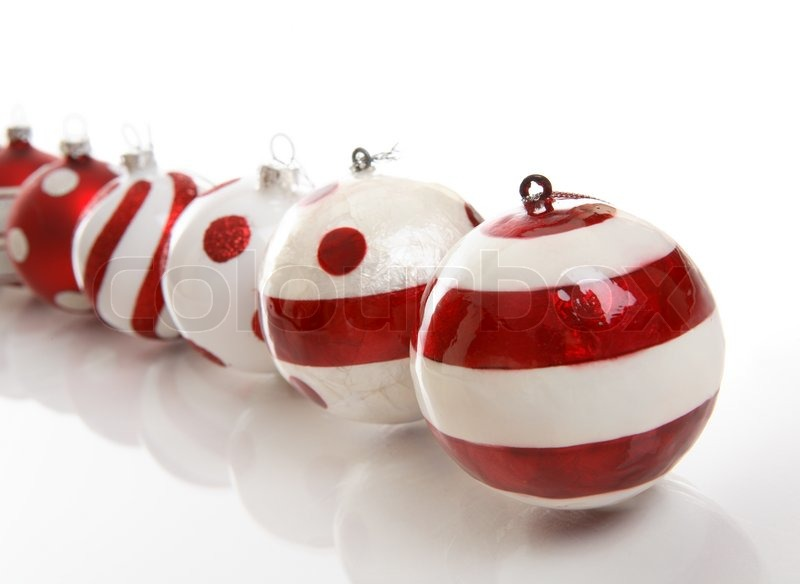 A selection of red and white christmas baubles on a white for White christmas baubles