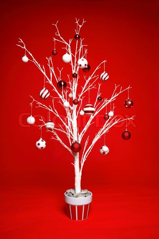 White modern Christmas tree decorated with various red and white themed christmas baubles balls on a red background, stock photo