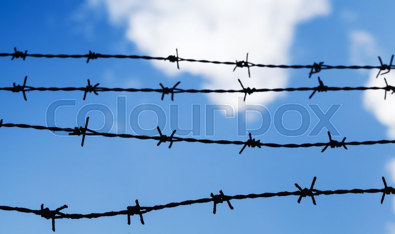 Black barbed wire fence over cloudy blue sky background, close up photo with selective focus, stock photo