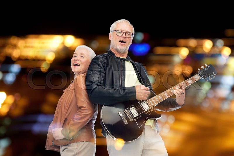 Music, age and people concept - happy senior couple with electric guitar singing over night lights background, stock photo
