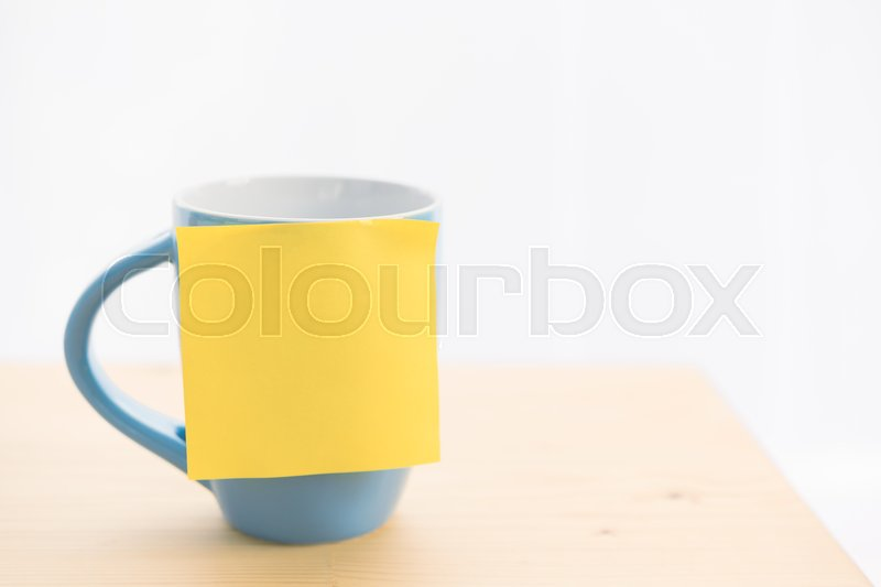 Blue coffee cup and post it for text on wood table top, stock photo