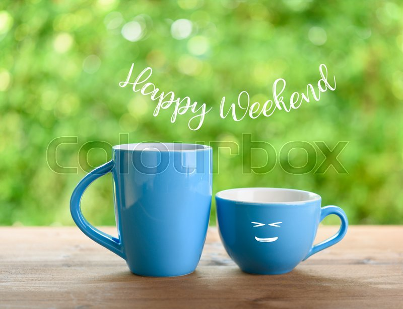 Blue coffee cups and happy weekend text on nature green blurred background, stock photo