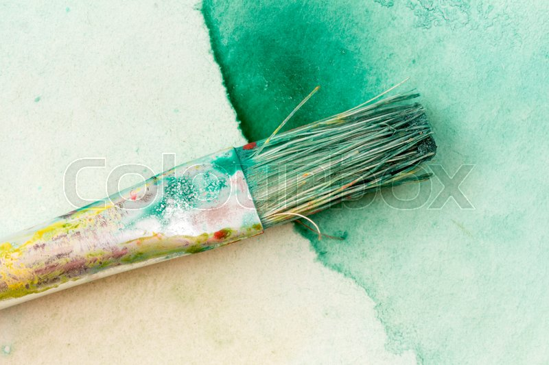 Watercolor brushe on green painting, close-up , stock photo
