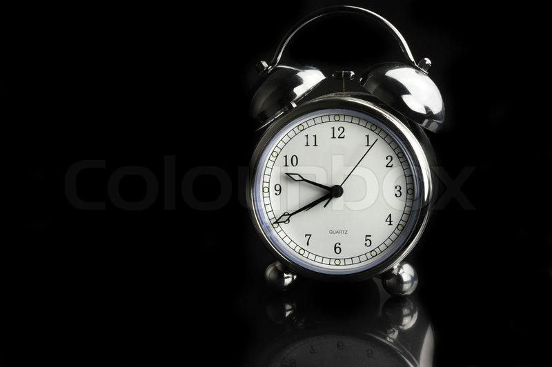 Silver antique alarm clock with white dial on a black background stock photo colourbox