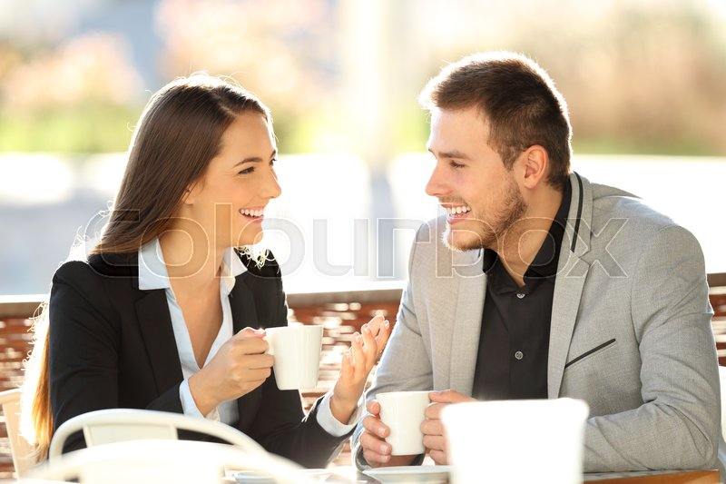 Two executives talking during a cofee break sitting in a bar terrace with a warm backlight, stock photo