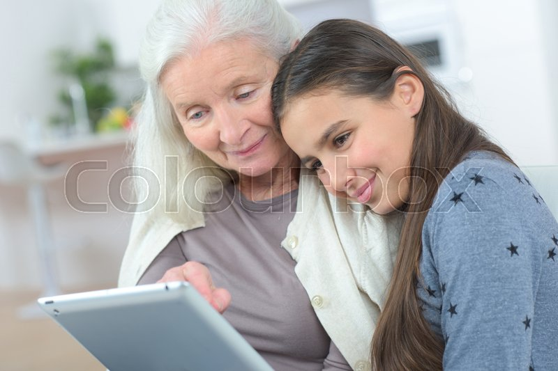 Stock image of 'Happy grandmother with grand daughter looking at a tablet'