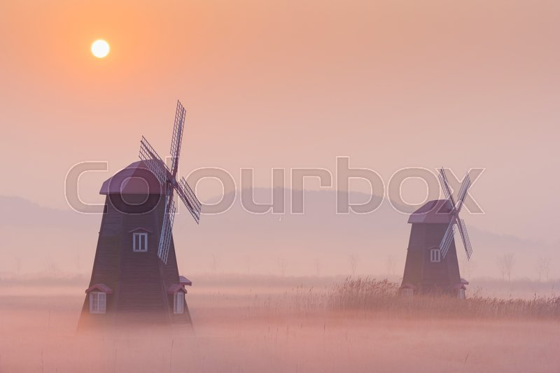 Stock image of 'autumn landscape misty morning on the wooden windmills in the park.'