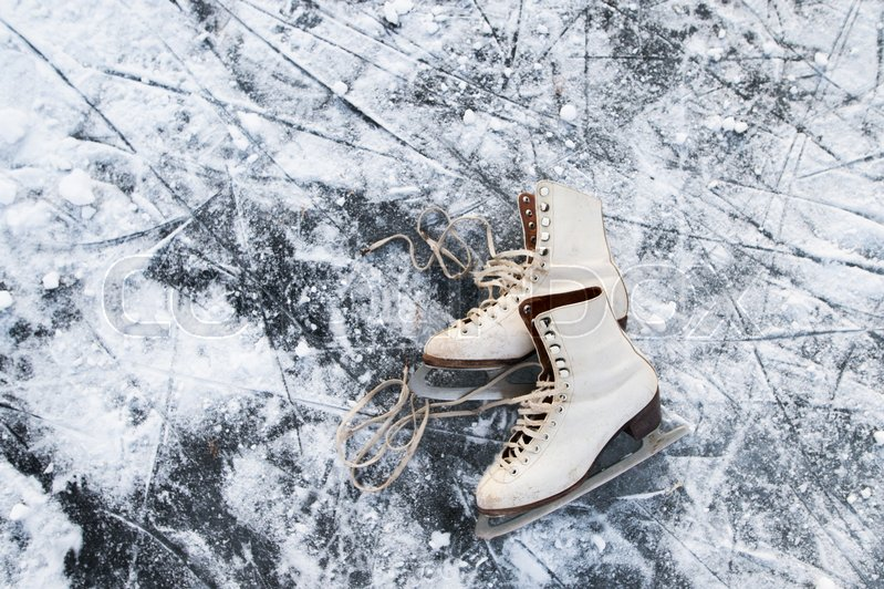 Old womans ice skates lying on the ice. Close up, stock photo