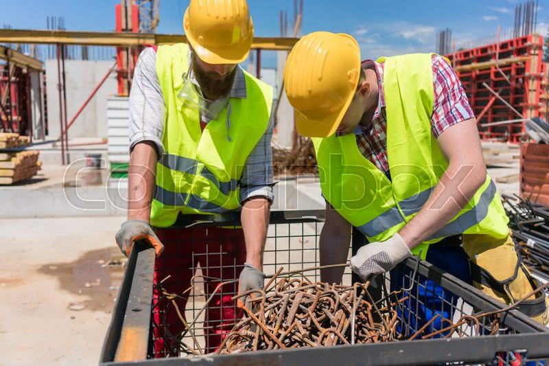 Two workers wearing yellow hard hats and safety reflective vests while checking a pile of rusty steel bars during work on the construction site, stock photo