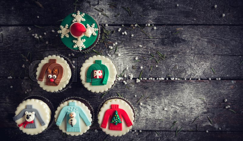 Stock image of 'Christmas decorative cupcakes on wooden background with blank space '