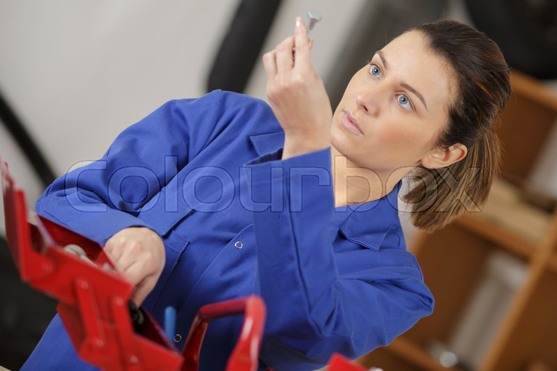 Woman looking for tool in her tool box, stock photo