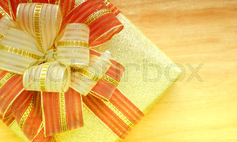 Gold gift box with red and gold ribbon on wood background. Close up. Top view, stock photo