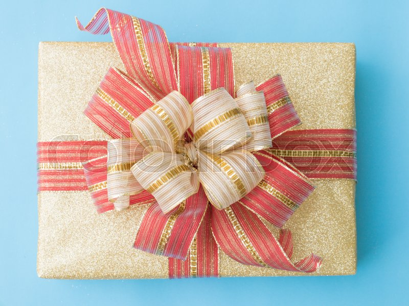 Gold gift box with red and gold ribbon on blue background. Close up. Top view, stock photo