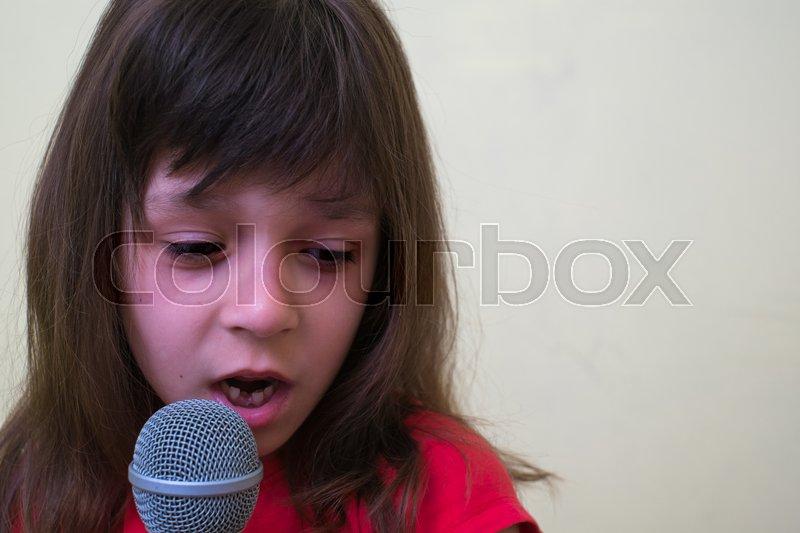 Girl with a microphone. little girl with a microphone. cute little girl singing with a microphone. karaoke. girl sings joyfully. girl singer. the little singer, stock photo