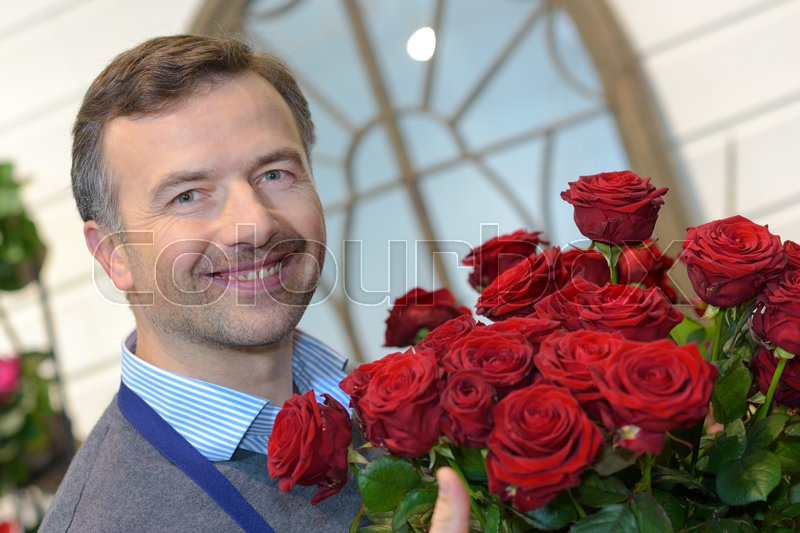 Male florist holding a pot of red roses, stock photo