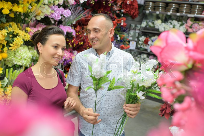 Man sells flowers in the flower shop, stock photo