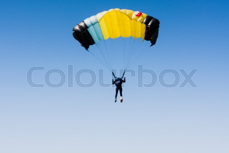 Skydiver in clean sky with copy space. Yellow parachute, stock photo
