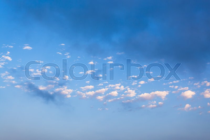 Little white clouds and rainy gray cloud in blue evening sky over Crimean Southern Coast in september, stock photo