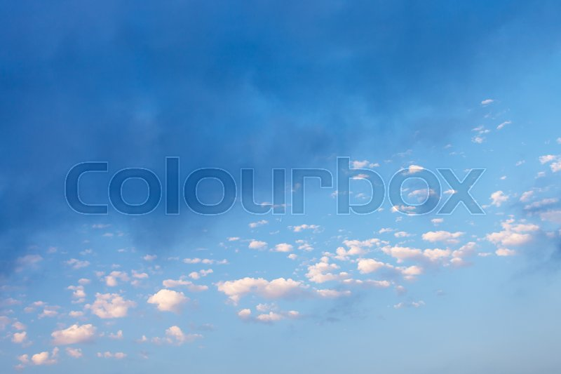 Many little white clouds and rainy gray cloud in blue sky over Crimean Southern Coast in september evening, stock photo