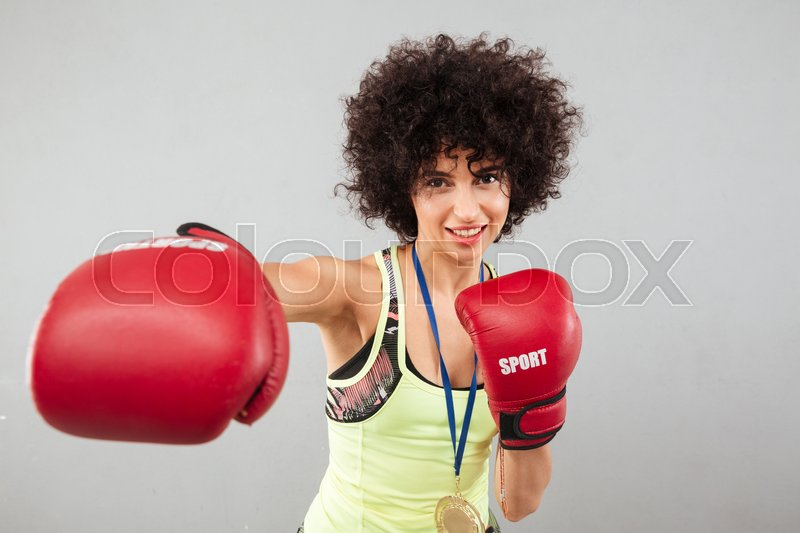 Smiling carefree sports woman boxing at the camera over gray background, stock photo