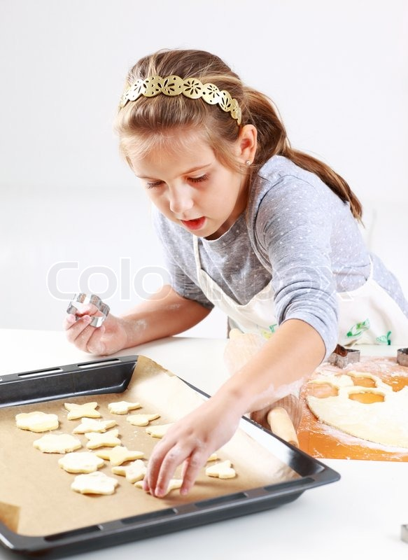 Stock image of cute girl baking cookies for christmas