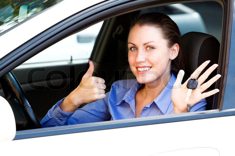 Pretty female driver in a white car showing the car key, stock photo
