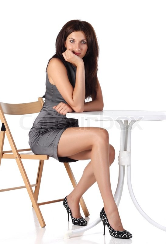 Girl Sitting On A Chair Near The Table Stock Photo
