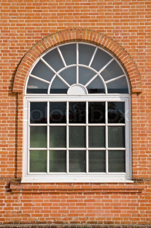 White painted wood arched window in a red brick wall | Stock Photo