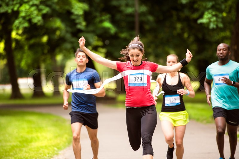 Beautiful young woman running in the crowd crossing the finish line, stock photo