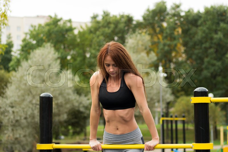 Caucasian brunette girl leaned on sports bars. Sexy fitness young woman at outdoor work out gym, stock photo