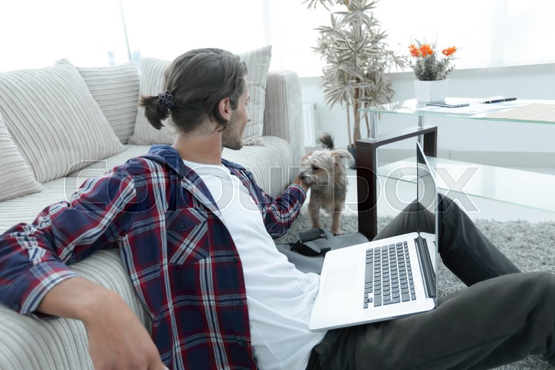Stylish young man stroking his pet and working on laptop in living room. concept of a lifestyle, stock photo