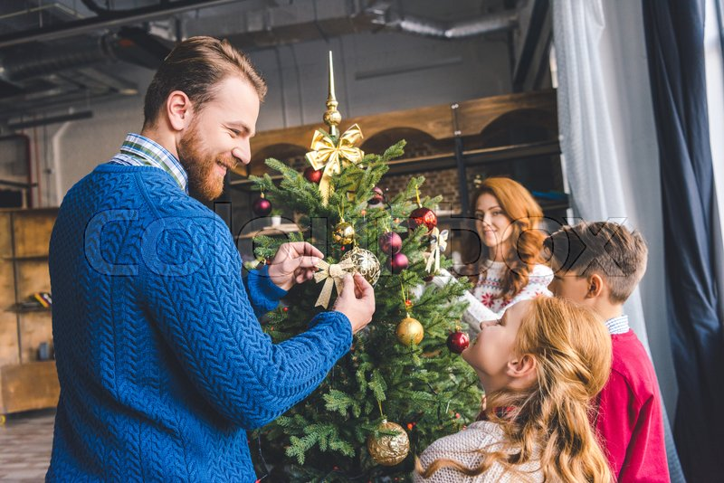 Young happy family decorating christmas tree at cozy modern apartments, stock photo