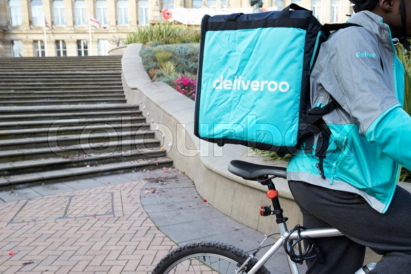 Birmingham, UK - 6 November 2016: Food Delivery Person Wearing Backpack Riding Bicycle, stock photo