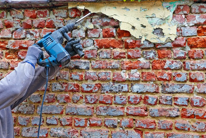Worker with electrical hammer cleaning red brick wall outdoor, stock photo