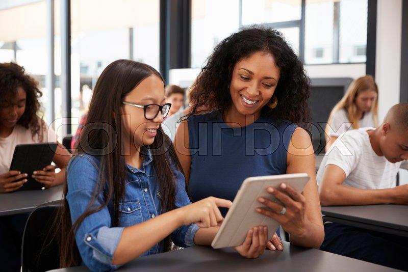 Teacher Helping Teenage Schoolgirl With Tablet Computer Stock Photo Colourbox
