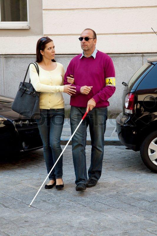 Eine Junge Frau Tr 228 Gt Einen Blinden Mann Stockfoto