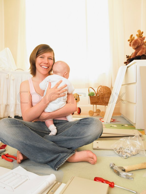 Woman with baby building furniture, stock photo