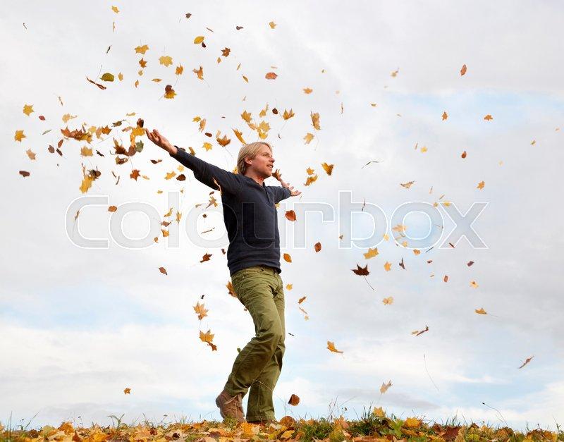 Man walking through flying autumn leaves, stock photo