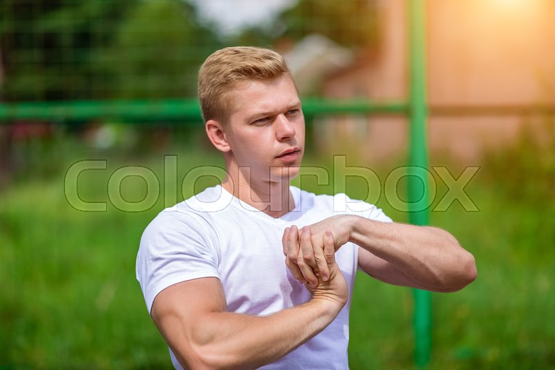 Stretches the muscles of the teams. The coach man does the warm-up, in the city on the nature, in the summer in a T-shirt. Athlete in nature. The concept of a healthy lifestyle. Exercise in the fresh air, stock photo