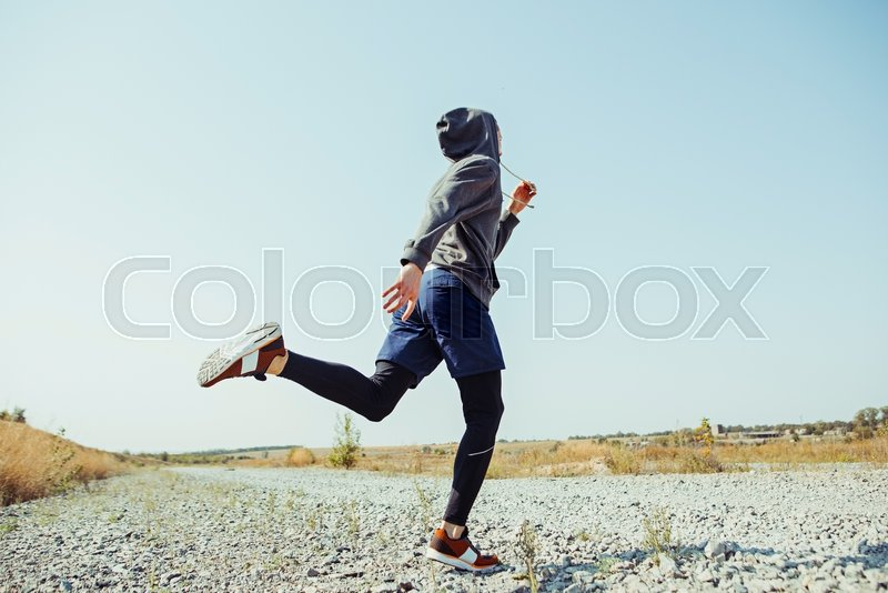 Running sport. Man runner sprinting outdoor in scenic nature. Fit muscular male athlete training trail running for marathon run. Sporty fit athletic man working out in compression clothing in sprint, stock photo