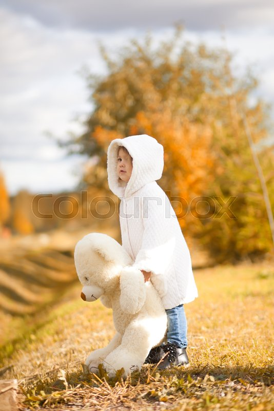 Little girl walking with big teddy bear toy in the autumn park, fall outdoors, present for little child, stock photo