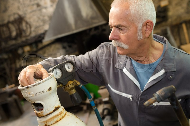 Technician dealing with steel cylinder with gas, stock photo