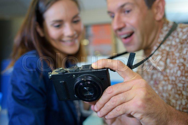 Man and woman looking at display of digital camera, stock photo