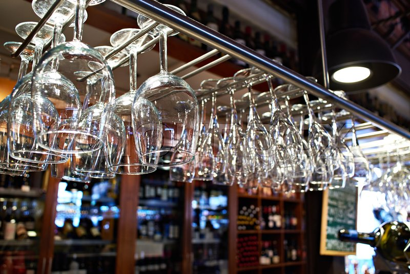 Empty wine glasses hanging above the bar counter, stock photo