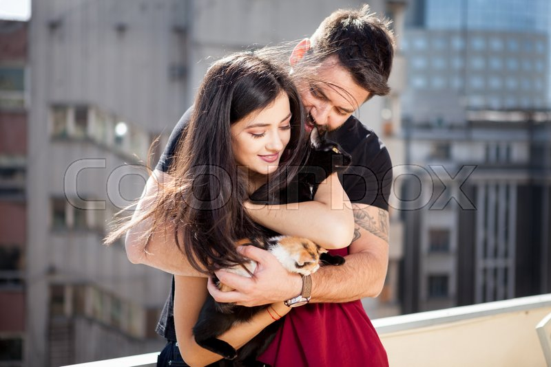 Young couple holding cats in hands on the terrace. Relax and love. Animal care. Animal lovers, stock photo