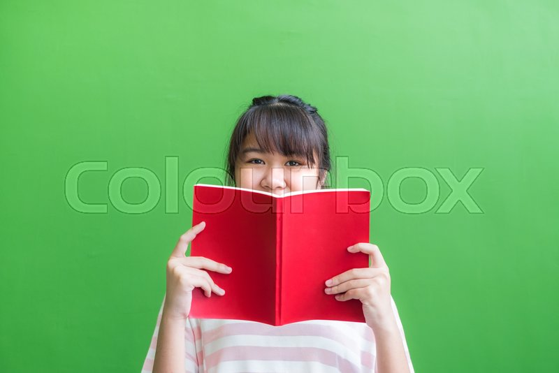 Teenager asia girl holding red book cover face with thinking action against green vivid wall,Leave copy space upper head to adding content of design for advertising education campaign concept., stock photo