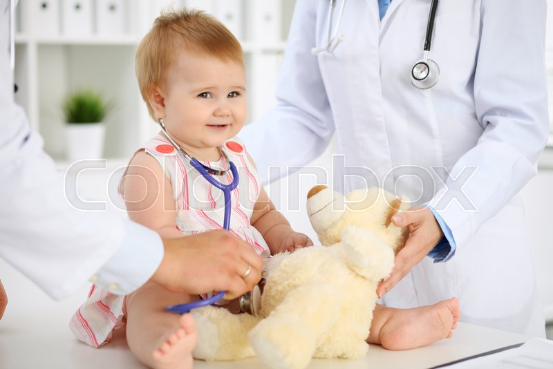 Happy cute baby at health exam at doctor\'s office. Toddler girl is sitting and keeping stethoscope and teddy bear, stock photo
