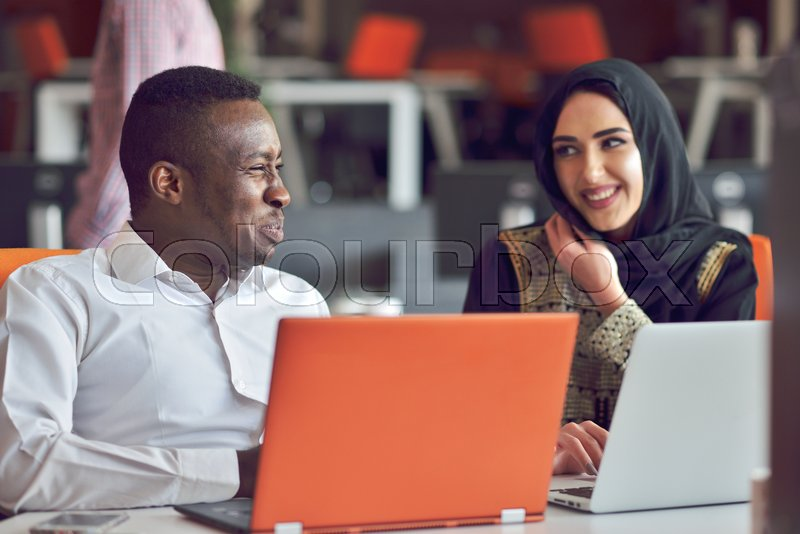 Multiracial contemporary business people working connected with technological devices like tablet and laptop, talking together - finance, business, technology concept, stock photo